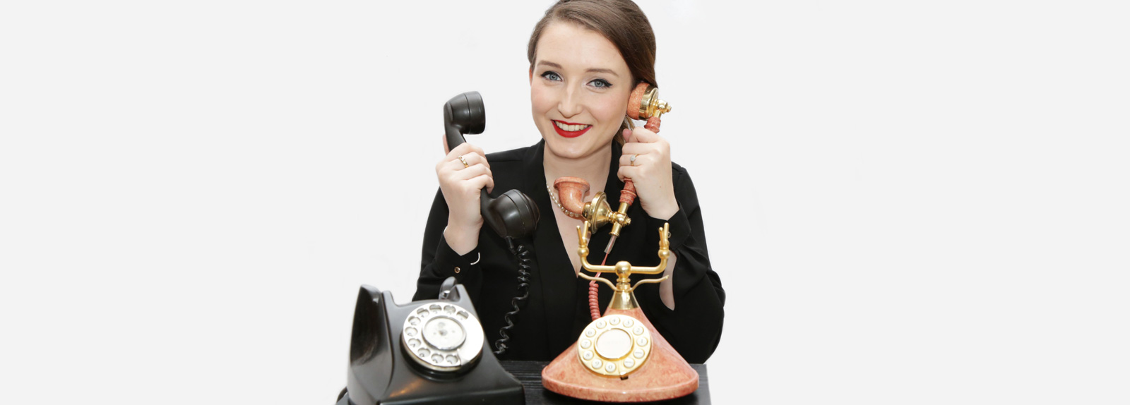 Smiling, smart young woman answering traditional telephone sets