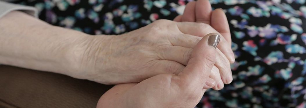 A photograph indicating the care of someone for an older person